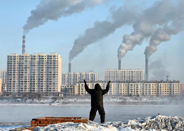 An elderly man exercises in the morning as he faces chimneys emitting smoke behind buildings across the Songhua river in Jilin.