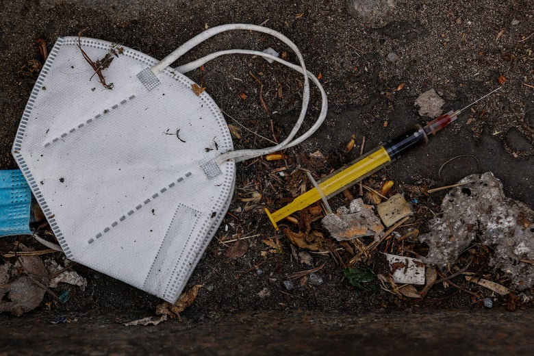 A mask and a syringe are seen on the ground.