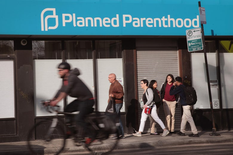 Pedestrians and a cyclist move past a Planned Parenthood awning on a building.