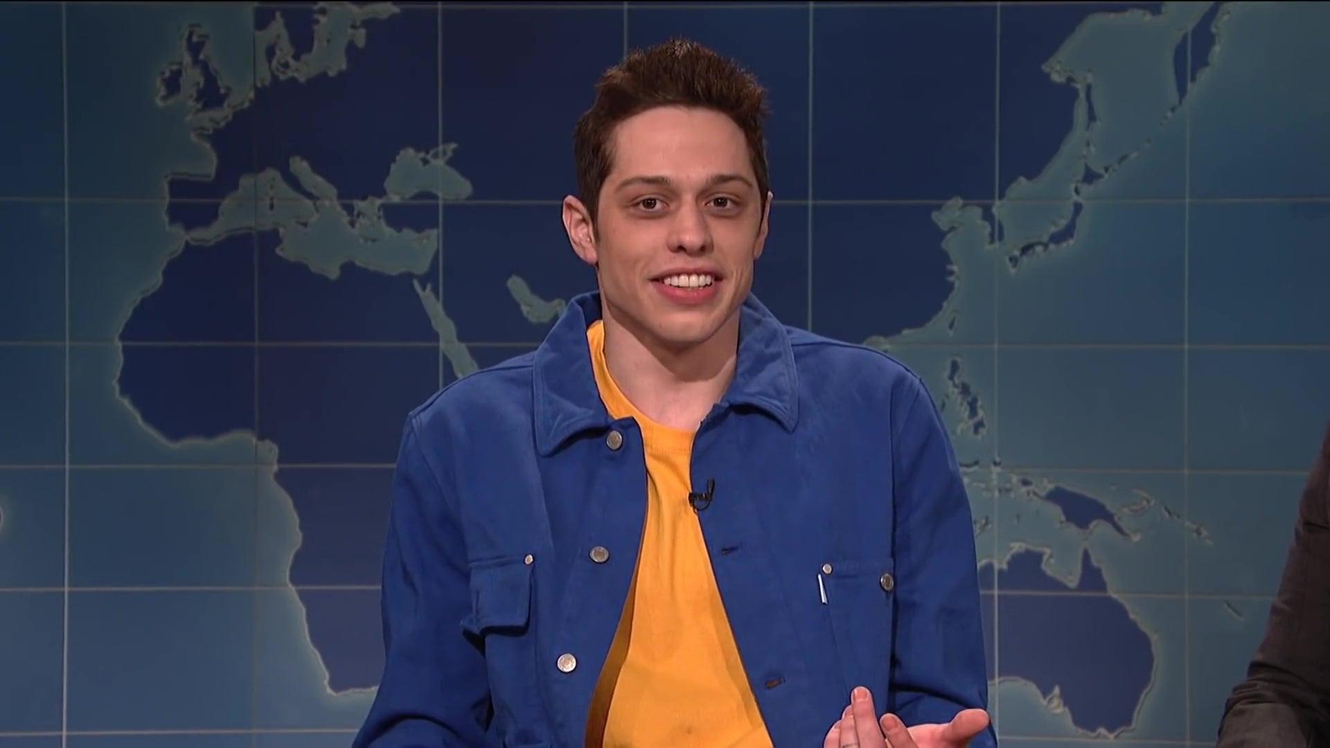 Pete Davidson sitting at the Weekend Update desk.