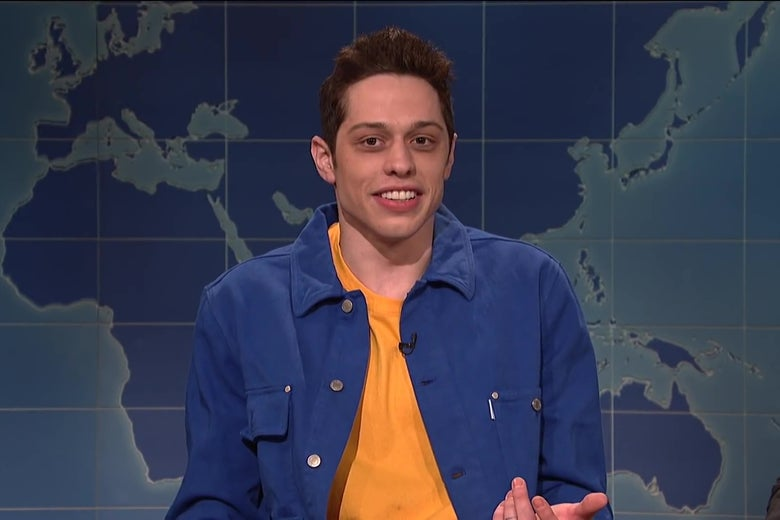 Pete Davidson sitting at the Weekend Update desk.