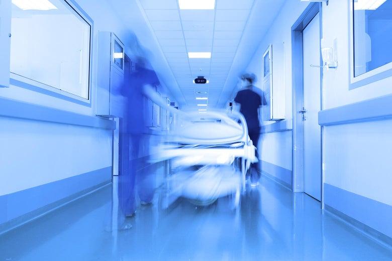 A gurney is wheeled down a hallway.