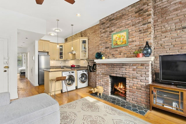 A living room with a fireplace and a washer dryer in the kitchen