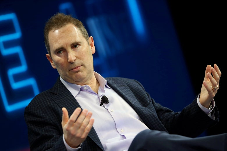 Andy Jassy, seated, gestures as he speaks onstage at a conference.