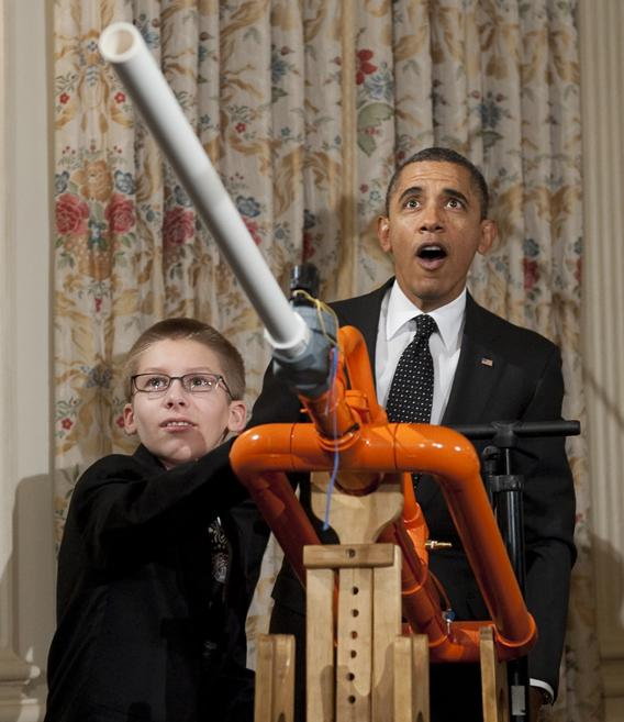 "President Barack Obama reacts as 14-year-old Joey Hudy of Phoenix launches a marshmallow from Hudy's ""Extreme Marshmallow Cannon"" during a tour of the White House Science Fair"