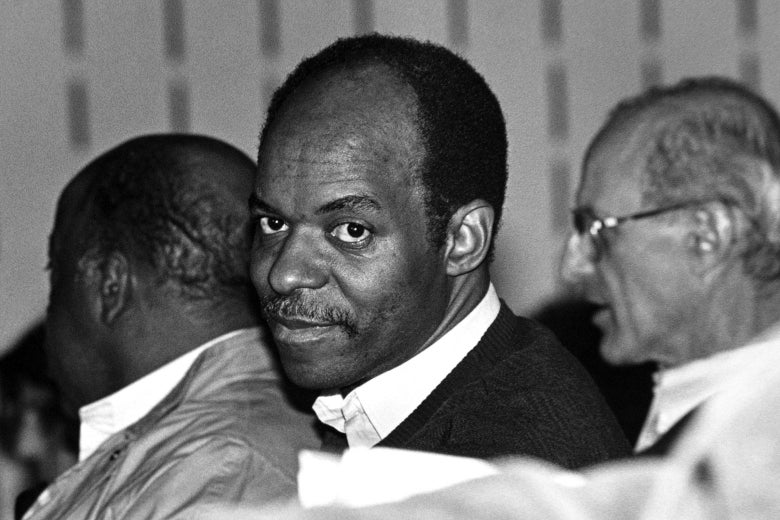 Lewis, seated between two others, looks toward the camera in a black-and-white photo.