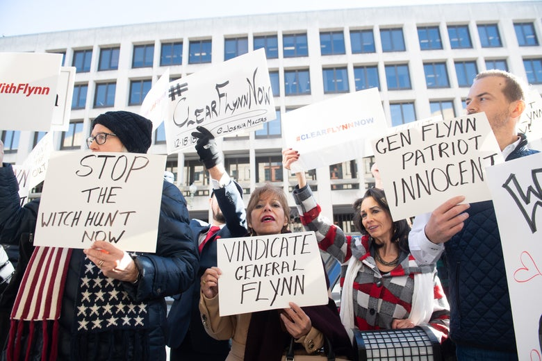 Protesters hold signs reading STOP THE WITCH HUNT NOW, VINDICATE GENERAL FLYNN and GEN. FLYNN PATRIOT INNOCENT.