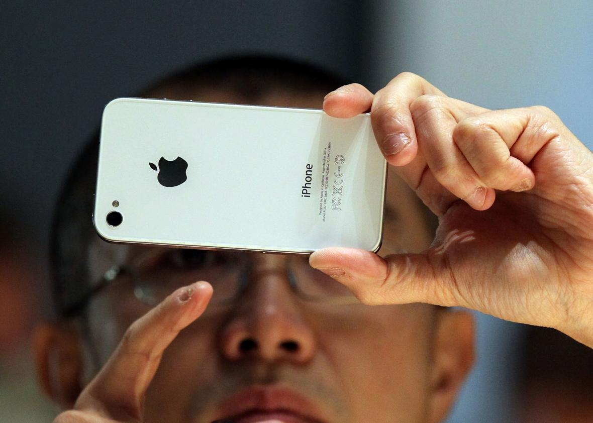 A member of the media inspects the then-new iPhone 4 in 2010. Apple can't access the contents of newer iPhones, but the government thinks it should turn over data on older iPhones when requested.