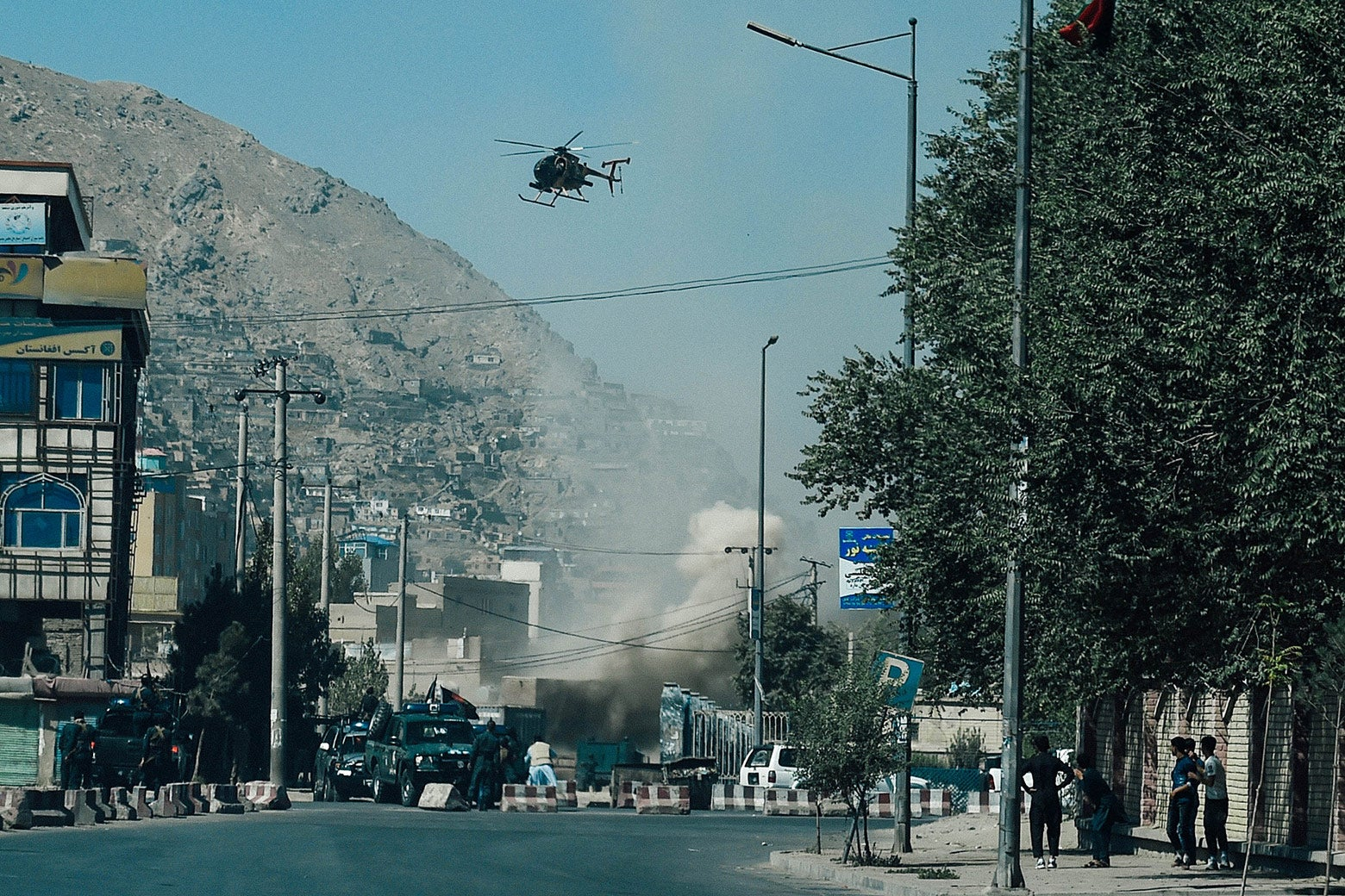 Smoke rises above a street with a helicopter overhead.