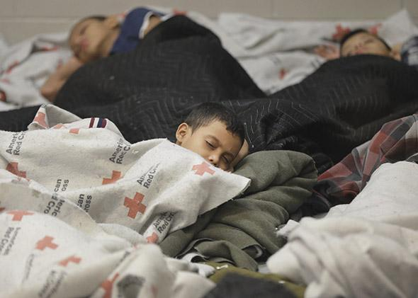 Detained children sleep in a holding cell at a U.S. Customs and Border Protection processing facility in Browsnville, Texas, on June 18, 2014.