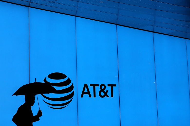 A man walks with an umbrella outside of AT&T corporate headquarters