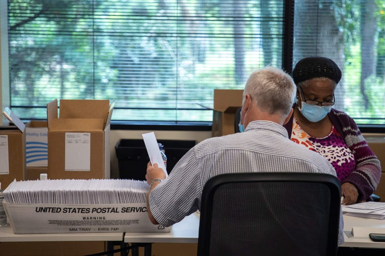 Two election officials sit at a table with boxes of absentee ballot materials and USPS containers.