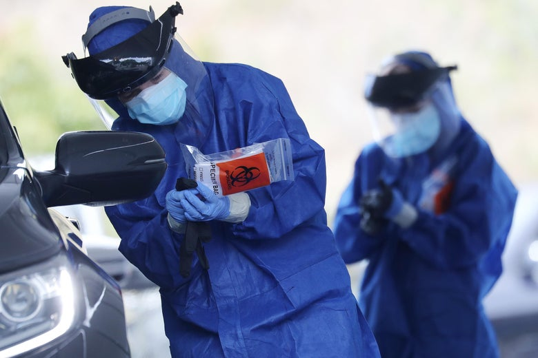 A volunteer  holds a specimen bag while conducting drive-through coronavirus testing at Malibu City Hall on April 8, 2020 in Malibu, California.