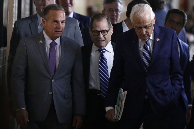 The three men walk side by side in a hallway looking busy and important.