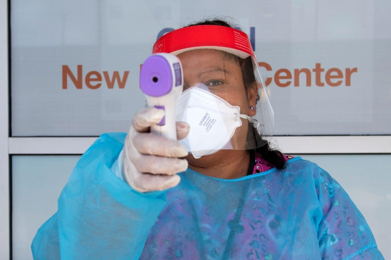 A health worker dressed in personal protective equipment points a thermometer at the camera.