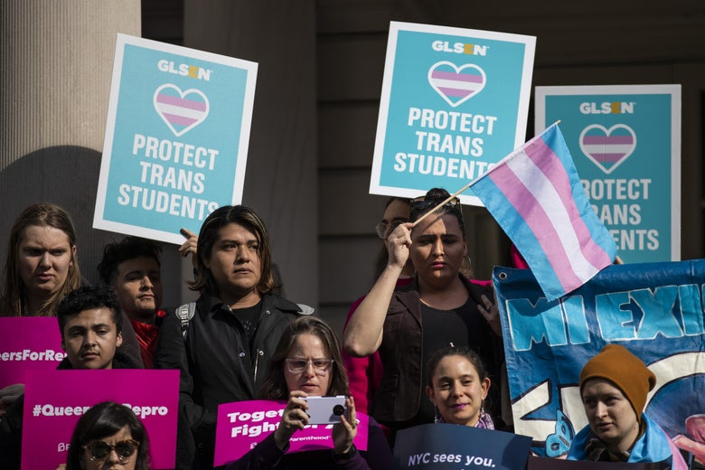 LGBTQ activists hold up signs supporting trans students