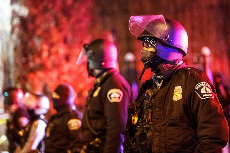 Police stand guard outside, wearing helmets and heavy jackets