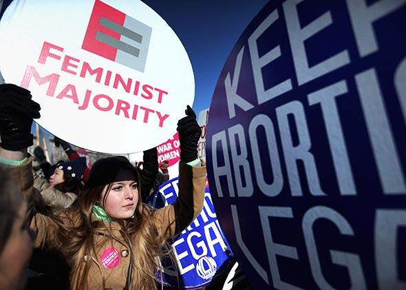 Pro-choice activist and Feminist Majority Foundation intern Jade Reindl holds a sign as participants in the annual March for Life arrive in front of the U.S. Supreme Court on Jan. 22, 2014, in Washington, D.C.