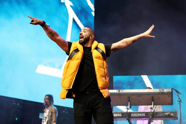 A man in a yellow puffy vest, black shirt, and black pants holds out his arms with his mouth open. He is performing on a stage, pointing a finger out with his right hand toward the audience.
