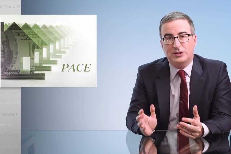 """John Oliver sits at a glass anchorperson desk, in front of a graphic reading """"PACE."""""""