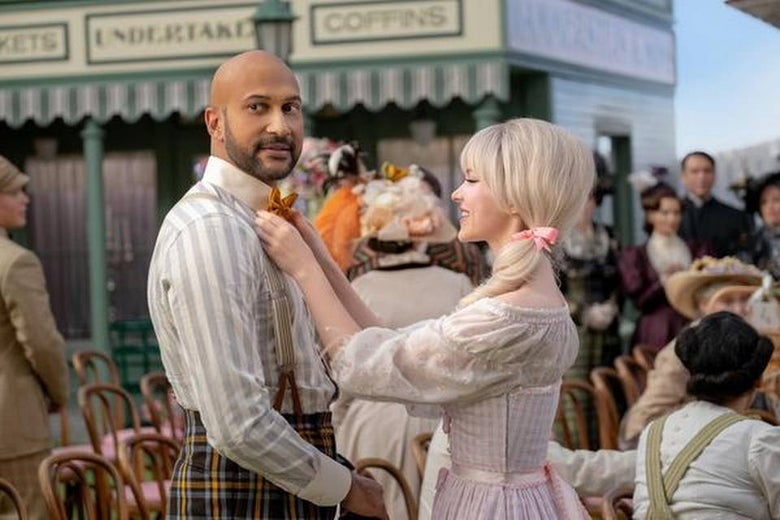 Dove Cameron adjusts the bow tie of Keegan-Michael Key. They are wearing turn-of-the-century garb straight out of a Golden Age musical surrounded by people dressed similarly.