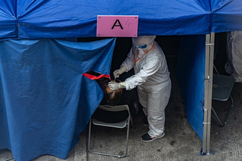 A health worker in full protective gear administers a coronavirus swab in a patient's nose in a makeshift tent.
