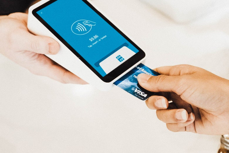 A credit card being inserted into a chip reader to make a payment.