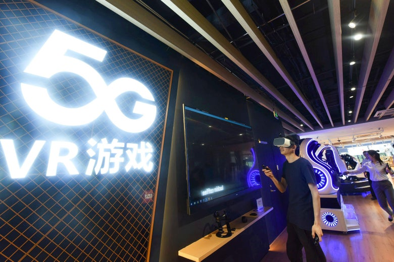 "A man wears a VR headset in front of a big neon sign that says ""5G VR."""