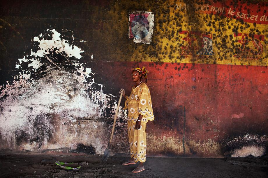 A woman poses for a picture in between cleaning the the destroyed main market in Gao, March 2, 2013.
