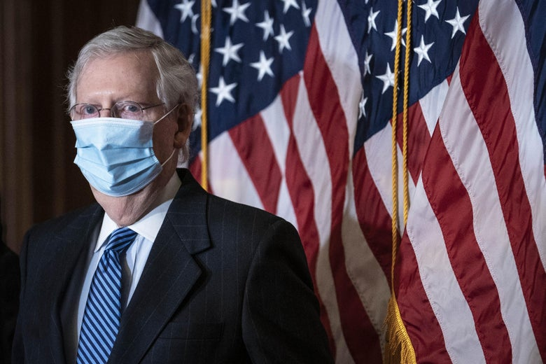 Mitch McConnell is seen wearing a face mask while standing front of U.S. flags.