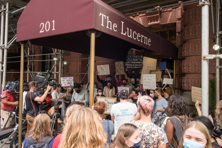 Protesters stand beneath and around an awning that says Lucerne.