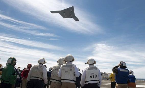 An unmanned Combat Air System flies over a flight deck.