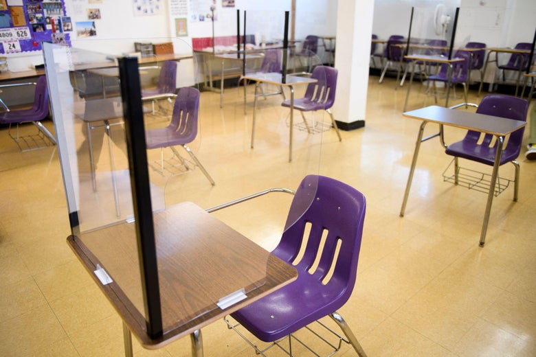 An empty classroom is seen, with desks and chairs distanced apart. Plexiglass dividers surround the desks.