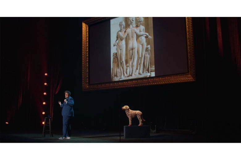 Hannah Gadsby onstage, in front of a screen displaying a photograph of a sculpture of the Three Graces.