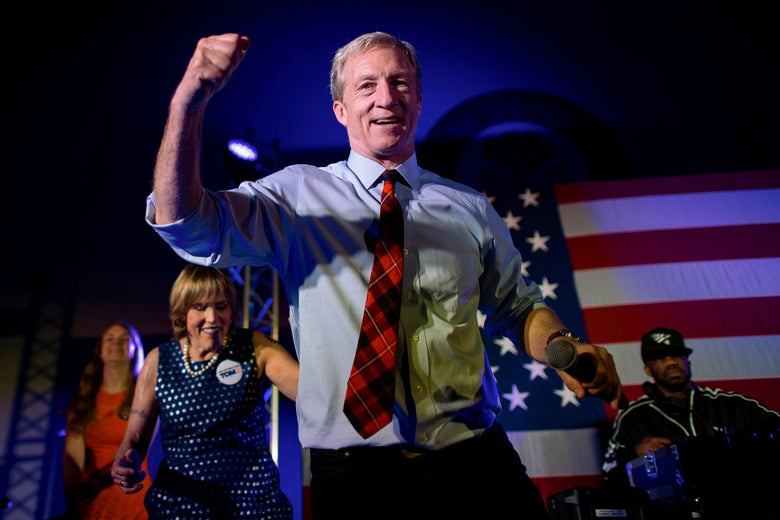 Tom Steyer dances onstage with rapper Juvenile on stage in front of an American flag.