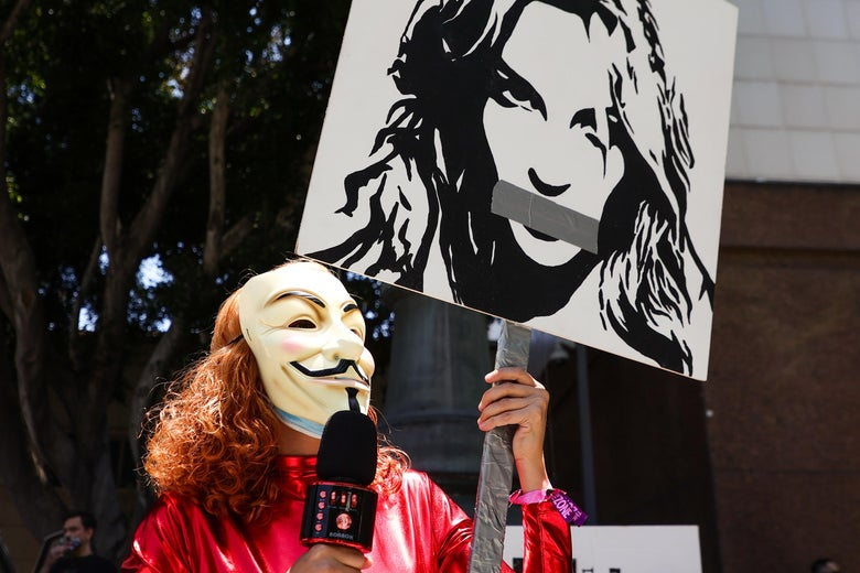 Person with red curly hair wearing a Guy Fawkes mask and a red shiny unitard holds a mic in one hand and a poster of Britney Spears with duct tape over her mouth in her other hand