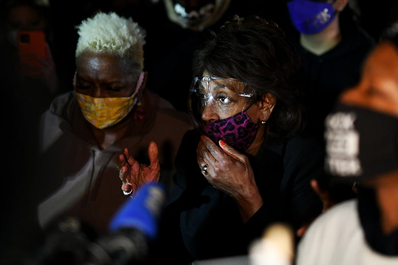 Maxine waters speaking at night in front of a large crowd.