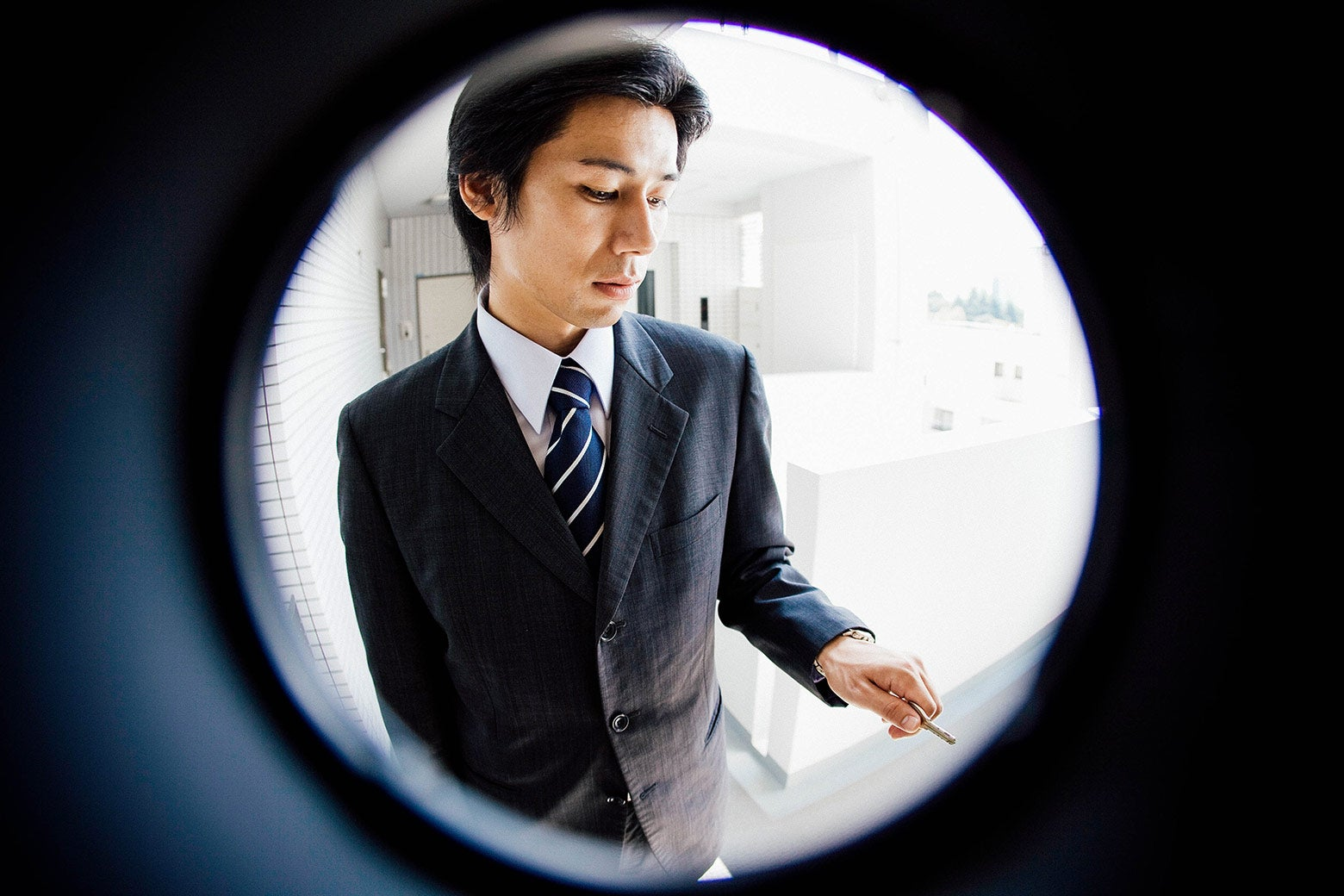 Fisheye peephole view of a man in a suit at the door.