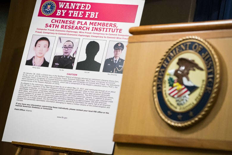 "A sign that says ""Wanted by the FBI"" with pictures of four men, next to a podium with the FBI seal."