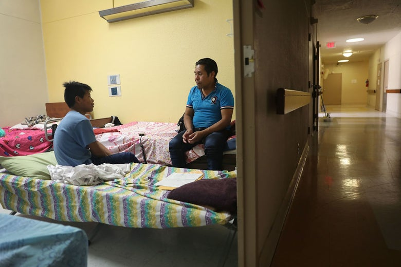 A man and his son speaking to each other while seated on dorm-style beds in a room off of a tile-floored hallway.