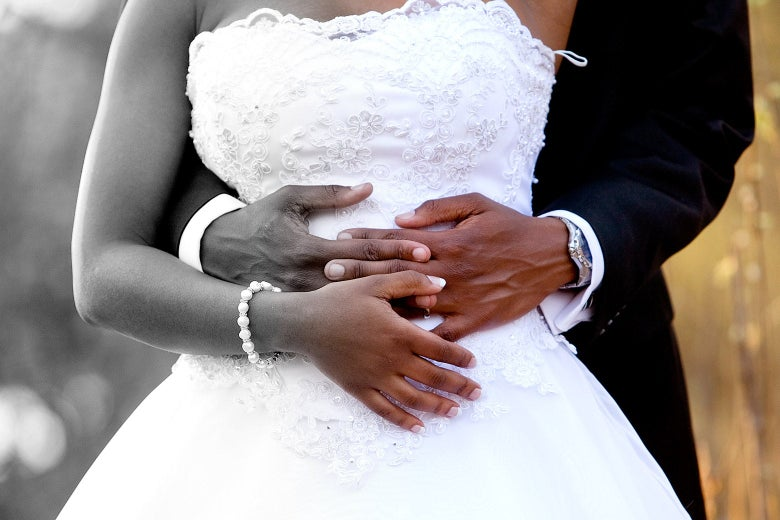 A bride and groom, with his arms wrapped around her waist. The left side of the image is greyscale, gradually transitioning to full color on the right.