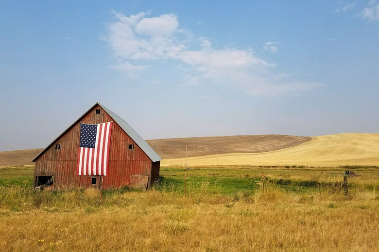 A brown barn with an American flag sits on rolling hills.
