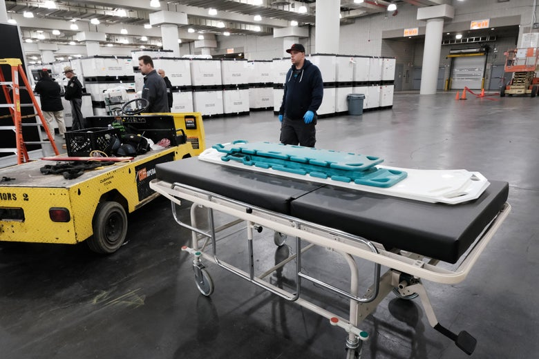 Workers load medical beds and other supplies into the Javits Center.
