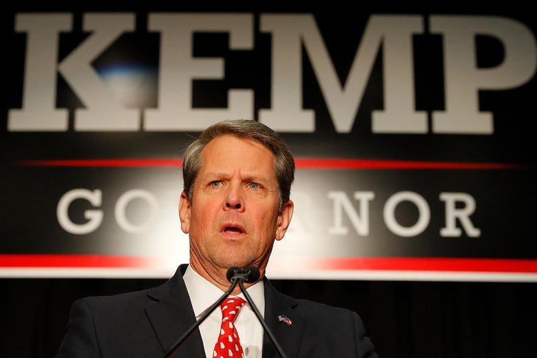 Brian Kemp in front of a Kemp/Governor sign.