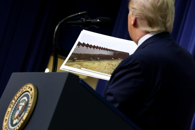 President Trump stands at a podium holding a photograph of border wall construction.