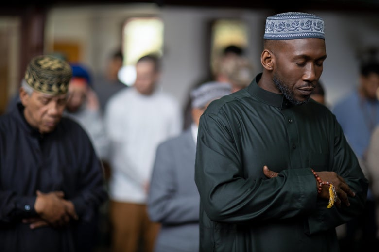 Mahershala Ali folds his hands and closes his eyes. Other Muslims stand behind him.