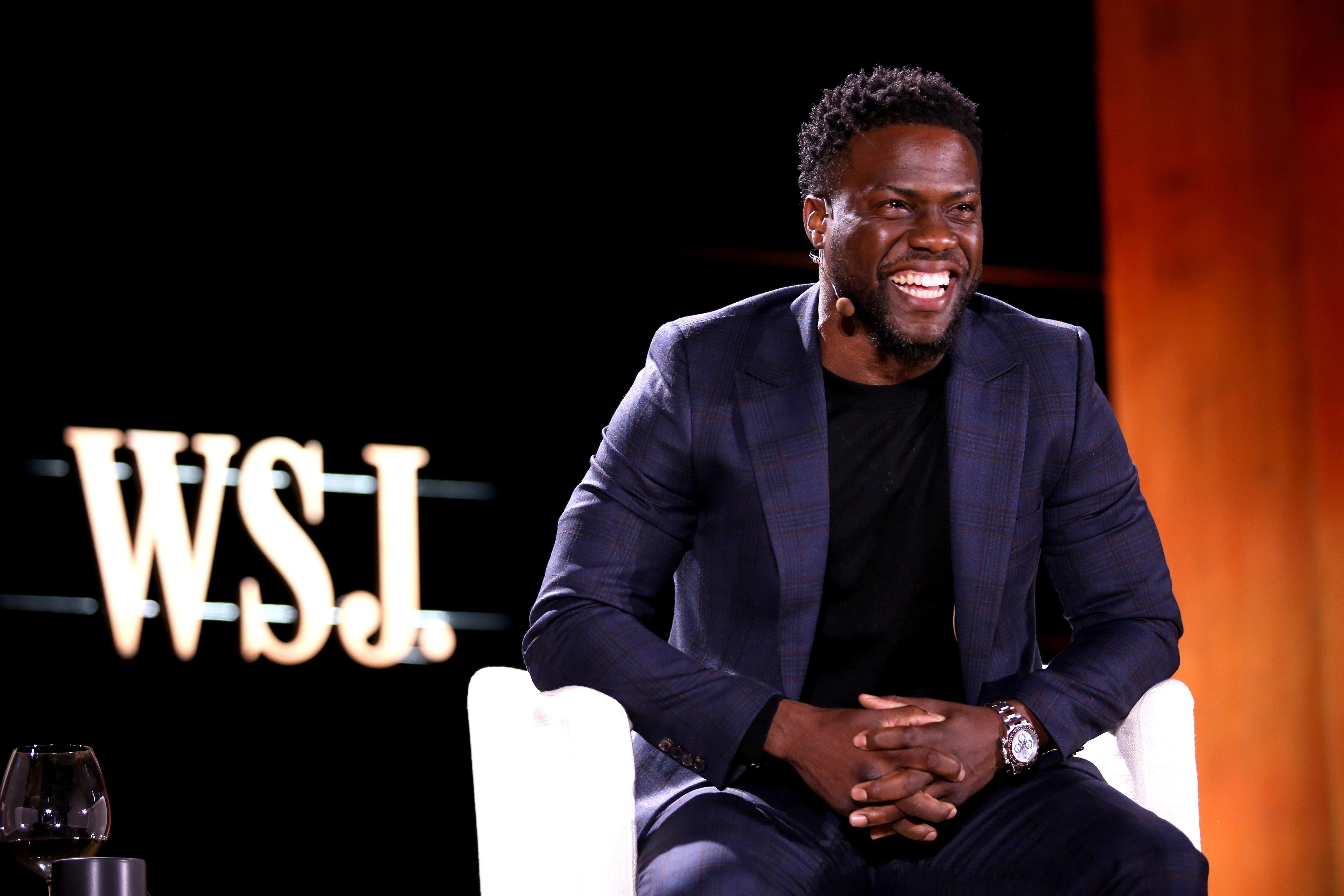 Kevin Hart sitting on a stage, smiling and laughing.