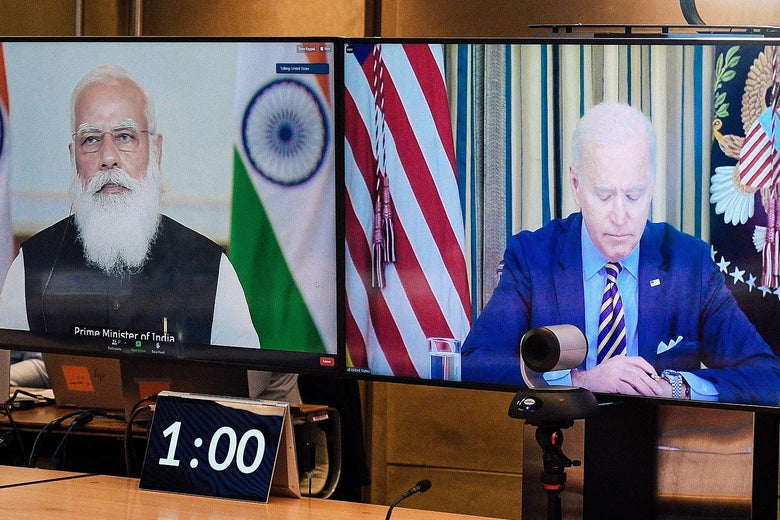 Modi and Biden seen in a videoconference on two TV screens.