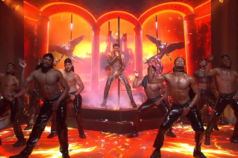 Lil Nas X performs on the SNL stage, which has been made up to look like hell. A line of shirtless black men wearing shiny black pants dance around him.
