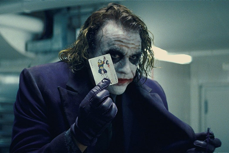 Heath Ledger as the Joker in The Dark Knight. He wears smeared, clown-like makeup and holds a playing card.